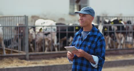 Farmer-Using-Digital-Tablet-While-Looking-At-Cows-3