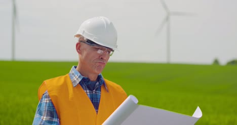 Engineer-Analyzing-Plan-While-Looking-At-Windmill-Farm-Eco-Energy-Concept-2
