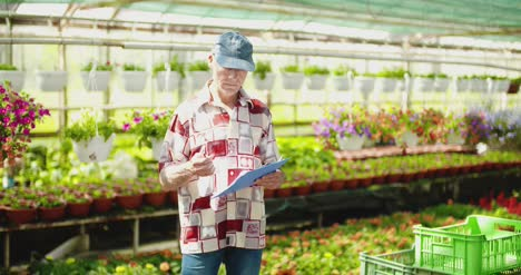 Researcher-Examining-Potted-Plant-At-Greenhouse-1