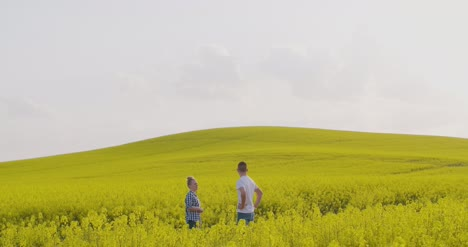 Farmers-Discussing-Over-Digital-Tablet-At-Rapeseed-Field-2
