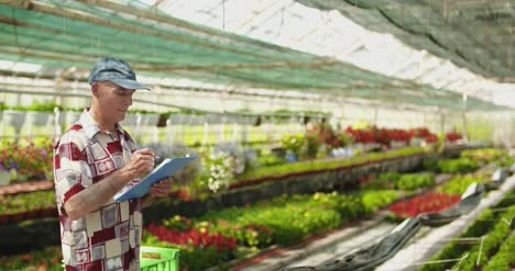 Researcher-Examining-Potted-Plant-At-Greenhouse-2