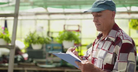 Researcher-Examining-Potted-Plant-At-Greenhouse-3