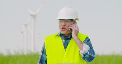 Frustrated-Male-Engineer-Talking-On-Phone-At-Farm