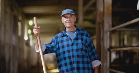 Confident-Mature-Male-Farmer-Holding-Pitchfork-In-Stable-5