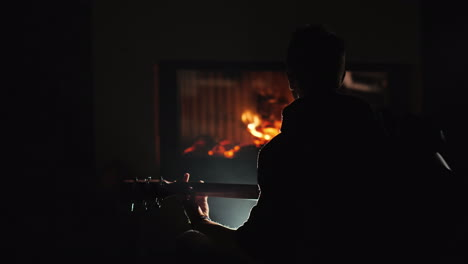 A-Young-Man-Plays-The-Guitar-Sitting-Alone-By-The-Fireplace