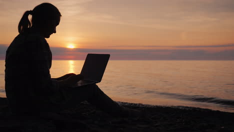 Silhouette-Of-A-Woman-Working-With-A-Laptop-By-The-Sea-At-Sunset