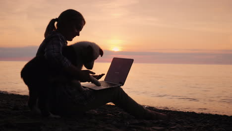 Woman-Blogger-Works-With-A-Laptop-Her-Distracted-Her-Puppy