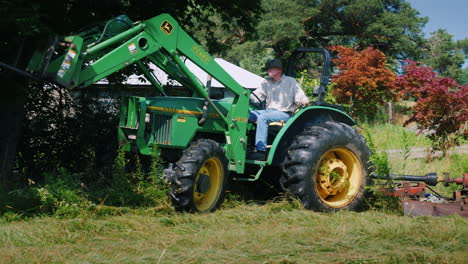 A-Man-On-A-Tractor-Mows-Tall-Grass-In-The-Yard