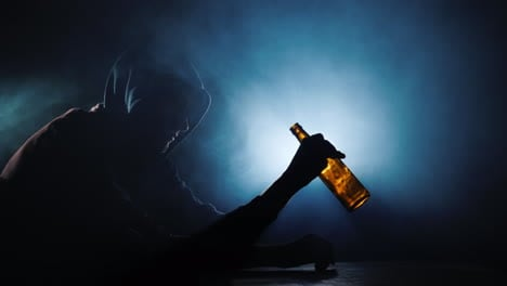 Silhouette-Of-A-Man-Sitting-With-An-Empty-Bottle-Of-Alcohol-In-His-Hand