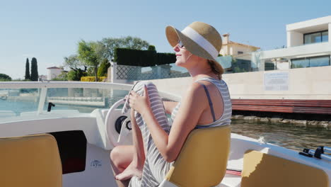 Holiday-Dreams-In-Europe-Woman-In-Sunglasses-And-Hat-Floating-In-A-Small-Boat-In-Empuriabrava-Spain