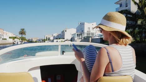 Always-Connected-Woman-With-A-Phone-In-His-Hand-On-A-Boat-Floats-On-The-Channel-The-Resort-Town-Of-E