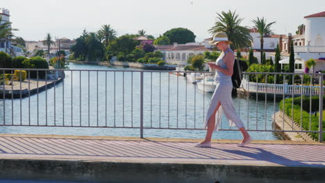 Young-Tourist-Woman-Walking-On-The-Bridge-Over-The-Canal-The-Area-Empuriabrava-Spain-Steadicam