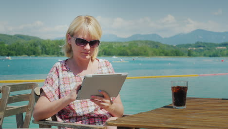 Technology-On-Vacation-Woman-With-Tablet-Sitting-At-A-Table-In-A-Cafe-On-The-Background-Of-The-Lake-