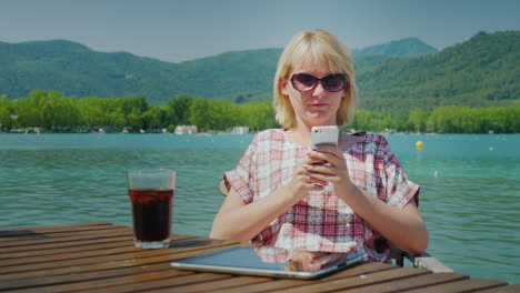 Young-Tourist-Woman-Relaxing-In-A-Beautiful-Location-By-The-Lake-And-Mountains-He-Uses-The-Phone-Sit