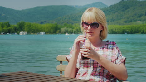 Young-Tourist-Woman-Relaxing-In-A-Beautiful-Location-By-The-Lake-And-Mountains-Drinks-Coke-From-A-Gl