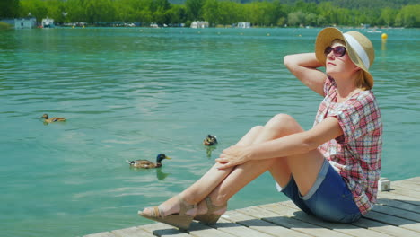 A-Woman-Tourist-Enjoying-Vacation-At-The-Lake-Where-Ducks-Swim-Resort-In-Spain