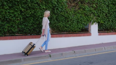 Woman-With-Travel-Bag-On-Wheels-Comes-To-The-Door-Of-The-Hotel-Arrival-At-The-Hotel-Or-On-Vacation-S