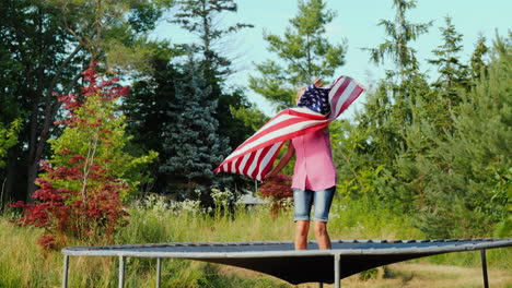 A-Woman-With-A-Flag-Of-The-Usa-Is-Jumping-On-A-Trampoline-Having-Fun-Independence-Day-And-A-Trip-To-