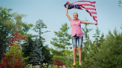 Attractive-Woman-With-The-Us-Flag-Jumping-On-A-Trampoline-In-Her-Backyard-Independence-Day-And-A-Tri