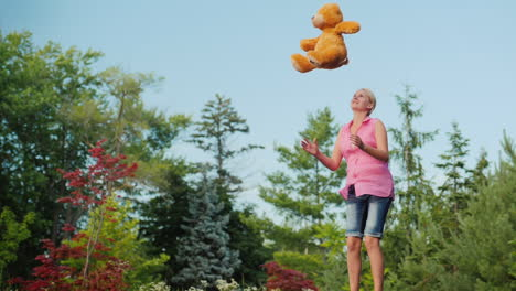 Middle-Aged-Woman-Having-Fun-Like-A-Child---Jumping-On-A-Trampoline-And-Throwing-Up-A-Teddy-Bear-Act
