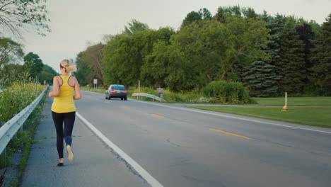 Middle-Aged-Woman-Runs-Along-The-Road-In-A-Typical-Suburb-Of-The-United-States-A-Healthy-Lifestyle-S