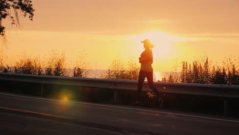 Silhouette-Of-A-Woman-Who-Runs-Along-The-Road-Along-The-Sea-At-Sunset-Active-Middle-Aged-People