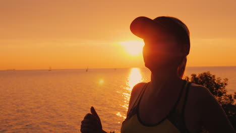 Healthy-Young-Woman-Jogging-In-The-Background-Of-The-Sea-And-The-Setting-Sun