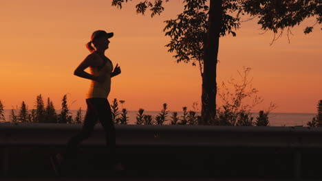 Active-And-Healthy-Lifestyle---Woman-Silhouette-Running-Along-The-Road-Along-The-Sea-At-Sunset