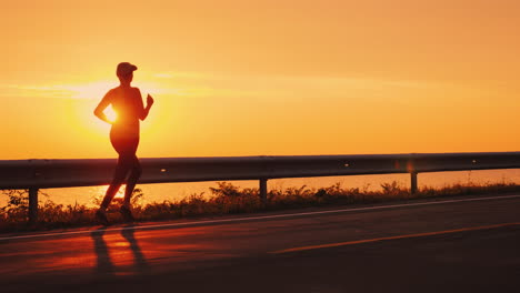 Slim-Athletic-Woman-Running-Along-The-Road-Against-The-Orange-Sky-And-The-Setting-Sun