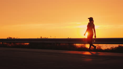 Walking-To-Promote-Health-In-A-Beautiful-Place-Silhouette-Of-A-Woman-Walking-Along-The-Road-Against-