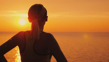 Purposeful-Female-Athlete-Looks-At-The-Sunset-Over-The-Sea-Rear-View