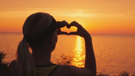 A-Woman-Looks-At-The-Sea-Where-The-Sun-Sets-Shows-A-Heart-Shaped-Figure