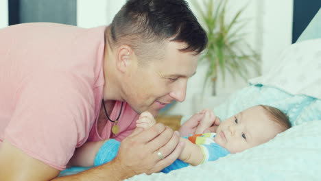 Young-Father-Playing-With-His-Son-Two-Months-He-Smiles
