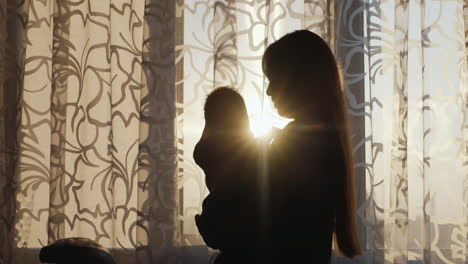 Silhouette-Mother-With-Baby-Standing-At-The-Window-At-Sunset-The-Sun-s-Rays-Shine-Beautifully