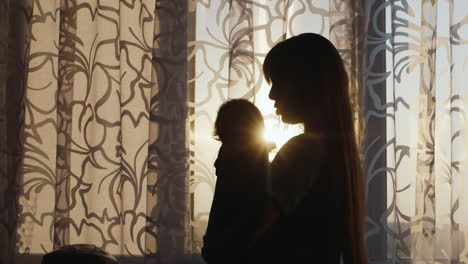 Silhouette-Of-A-Young-Mother-With-A-Child-At-The-Window-Swaying-The-Baby-In-Her-Arms-At-Sunset