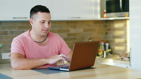 Young-Attractive-Man-Working-With-Laptop-At-The-Kitchen