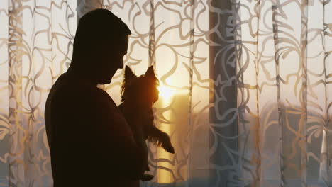A-Young-Single-Man-Standing-At-The-Window-Holding-His-Dog-Pensively-Looking-Into-The-Window-At-Sunse