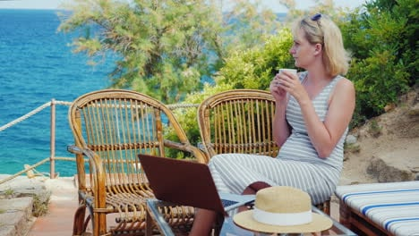 Young-Woman-Sitting-At-The-Table-With-A-Laptop-In-Front-Of-Sea-View-Lady-Freelancer-Working-At-The-B