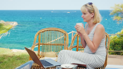 Young-Woman-Drinking-Coffee-Sitting-On-The-Terrace-Overlooking-The-Sea-Next-To-The-Laptop-Perfect-Fr