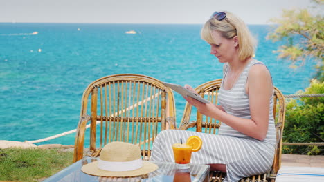 Young-Woman-Enjoys-The-Tablet-Sitting-On-The-Summer-Terrace-Cafe-Overlooking-The-Sea