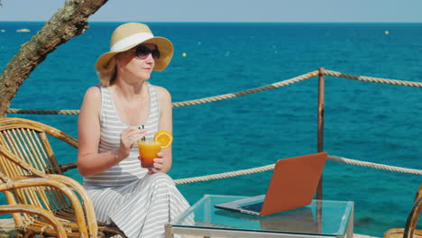 Woman-Tourist-Relaxing-In-A-Cafe-With-A-View-Of-The-Sea-And-Drinking-Cocktail-Nearby-Is-A-Laptop-On-