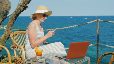 Woman-Tourist-Relaxing-In-A-Cafe-Overlooking-The-Sea-Enjoys-A-Smartphone-Standing-Next-To-A-Laptop