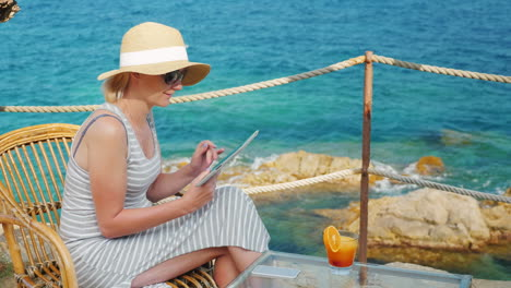 Business-Woman-On-Holiday-Sitting-In-A-Cafe-With-Scenic-Views-Of-The-Sea-It-Works-With-Tablet