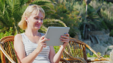 Woman-Tourist-With-The-Tablet-Says-He-Sits-In-A-Wicker-Chair-On-The-Background-Of-Palm-Trees-Always-