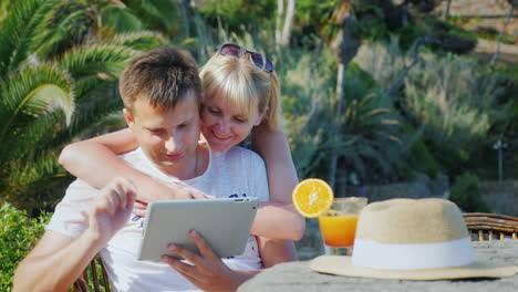 A-Married-Couple-With-A-Tablet-Obschaetsya-Have-Video-Smiling-At-The-Camera-Against-The-Backdrop-Of-