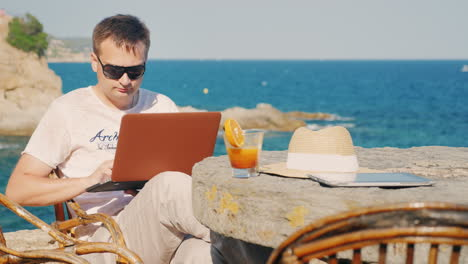 Man-In-Sunglasses-Work-With-A-Laptop-Against-The-Background-Of-The-Sea-At-A-Table-In-A-Cafe