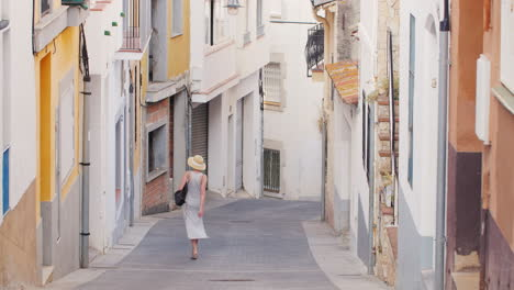 Woman-Tourist-In-Light-Dress-And-Hat-Goes-Down-The-Narrow-Streets-Of-The-Old-Mediterranean-City-In-S