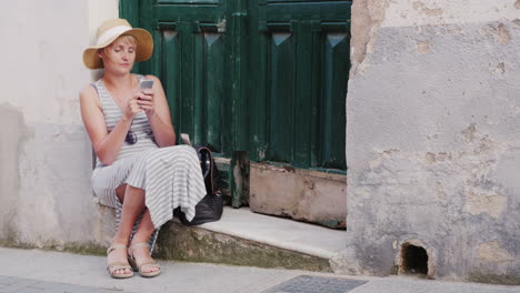 Woman-Tourist-Uses-Smartphone-He-Is-Sitting-On-The-Threshold-Of-The-Old-House-In-The-Resort-Town-Con