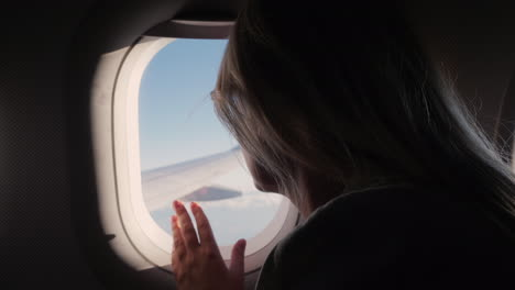 Silhouette-Of-A-Woman-Looks-Out-The-Porthole-At-The-Sky-And-The-Wing-Of-The-Plane-In-Flight-Enjoy-Th