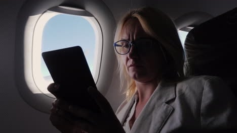 Business-Woman-Reads-An-E-Book-In-The-Plane-Business-Trip-Concept